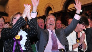 """UK Independence Party (UKIP) leader Nigel Farage (C) reacts sitting with UKIP MEP candidates Janice Atkinson (L) and Diane James (2R) and Ray Finch (R) as the South East England region results of the European Parliament elections are declared by the returning officer at Southampton Guildhall in Southampton, southern England, on May 25, 2014. Results rolled in for the European Parliament elections with all eyes on potential gains by Europe's increasingly popular anti-EU parties. Farage, leader of the eurosceptic UKIP on May 25 said his party was on course to cause a political """"earthquake"""" as it took the lead in the European parliament election in Britain. UKIP took seats in the South East region. AFP PHOTO / CARL COURT"""