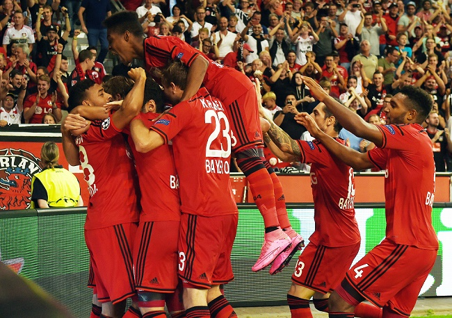 Leverkusen's Swiss forward Admir Mehmedi (covered) celebrates with teammates after scoring during the UEFA Champions League playoff football match between Bayer Leverkusen and SS Lazio, in Leverkusen, western Germany, on August 26, 2015.  AFP PHOTO / PATRIK STOLLARZ