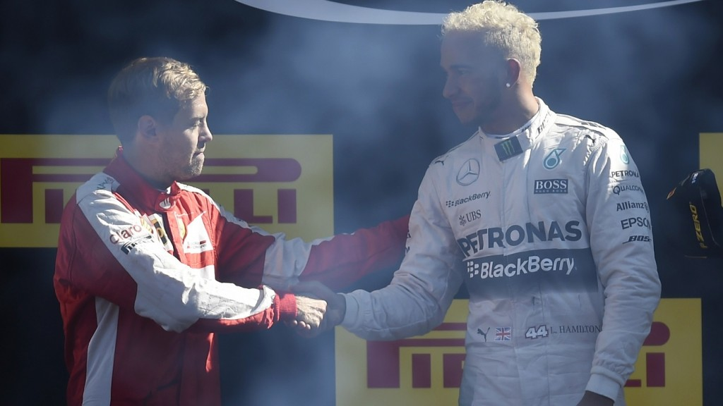 Mercedes AMG Petronas F1 Team's British driver Lewis Hamilton (R) shakes hands with second placed Ferrari's German driver Sebastian Vettel on the podium after winning the Italian Formula One Grand Prix at the Autodromo Nazionale circuit in Monza on September 6, 2015.  AFP PHOTO / OLIVIER MORIN