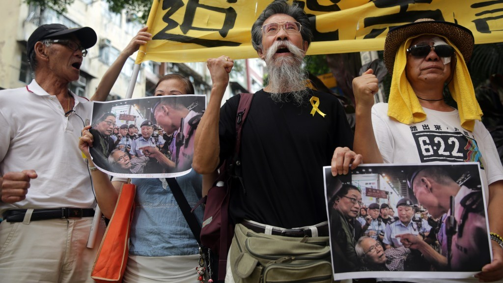 Protester hold pictures showing police confronting protesters during the 2014 occupy protests, as they gather in support of Nathan law and Joshua Wong who were to meet with police at the western district police station in Hong Kong on July 14, 2015. Wong, 18, the teenage face of the city's pro-democracy movement, and Nathan Law, leader of the major university student union, visited the station for a scheduled meeting with police. AFP PHOTO / ISAAC LAWRENCE