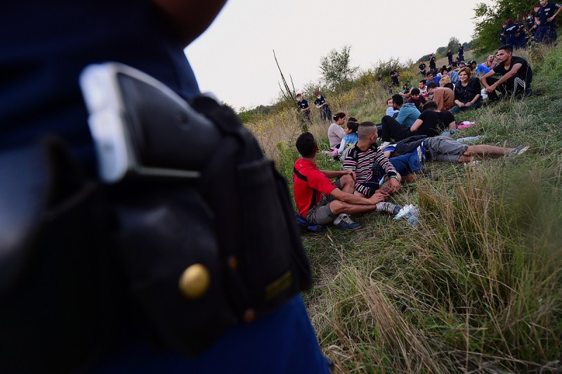 Hungarian policemen stand next to migrants from different countries sitting in the grass at the Hungarian-Serbian border on September 17, 2015 in Asotthalom near Roszke, Hungary. Clashes erupted at the flashpoint Roszke crossing on the Hungary-Serbia border on Wednesday, September 16, 2015, with police trying to block dozens of migrants massed on the Serbian side of the border from breaching a razor-wire fence. AFP PHOTO / ATTILA KISBENEDEK