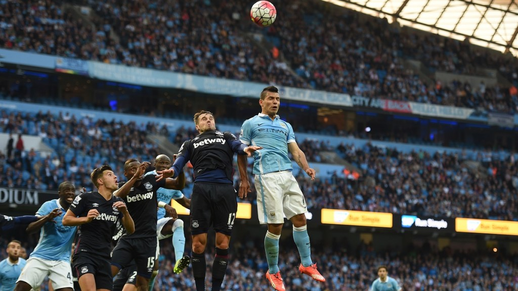 Manchester City's Argentinian striker Sergio Aguero (R) jumps for the ball against West Ham United's English midfielder Carl Jenkinson during the English Premier League football match between Manchester City and West Ham United at The Etihad Stadium in Manchester, north west England on September 19, 2015. AFP PHOTO / PAUL ELLIS  RESTRICTED TO EDITORIAL USE. No use with unauthorized audio, video, data, fixture lists, club/league logos or 'live' services. Online in-match use limited to 75 images, no video emulation. No use in betting, games or single club/league/player publications.