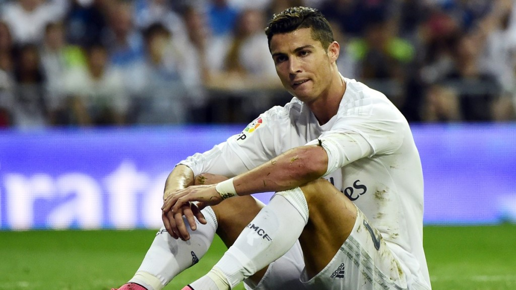 Real Madrid's Portuguese forward Cristiano Ronaldo sits on the ground during the Spanish league football match Real Madrid CF vs Malaga CF at the Santiago Bernabeu stadium in Madrid on September 26, 2015.    AFP PHOTO / PIERRE-PHILIPPE MARCOU