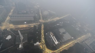 Lights illuminate the street circuit to be used for the Singapore Formula One as it is shrouded with haze on September 14, 2015. Helicopters water-bombed raging forest fires that have cloaked parts of Indonesia in thick haze and pushed air quality to unhealthy levels in neighbouring Singapore and Malaysia. AFP PHOTO / ROSLAN RAHMAN