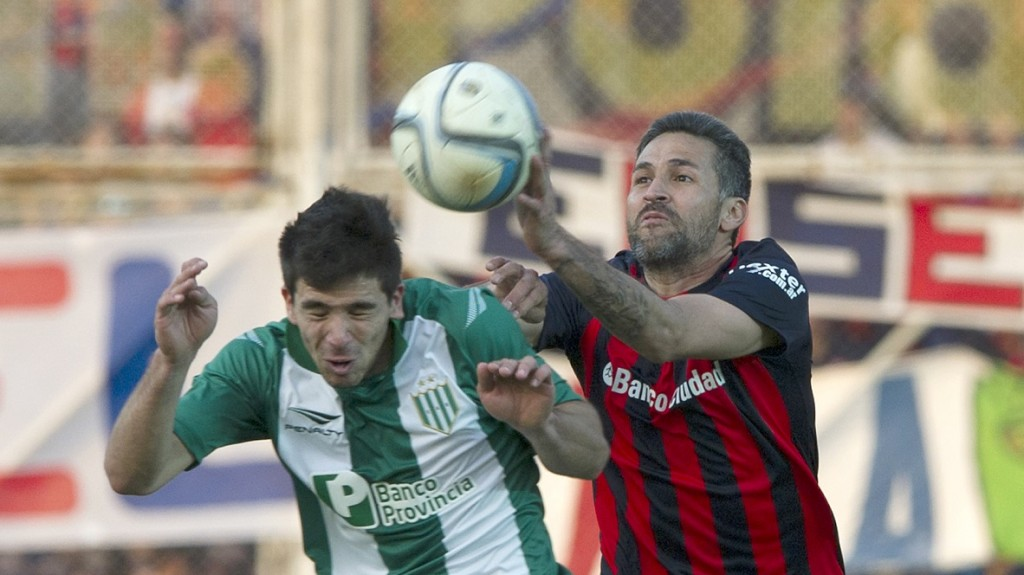 Banfield's forward Giovanni Simeone (L) vies for the ball with San Lorenzo's defender Mario Yepes  during their Argentina First Division football match at the Nuevo Gasometro stadium, in Buenos Aires, on August 30, 2015. AFP PHOTO / ALEJANDRO PAGNI