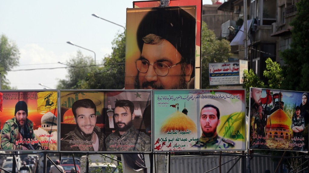 A portrait Hassan Nasrallah (top), the head of Lebanon's militant Shiite Muslim movement Hezbollah, and portraits of pro-government forces members killed in combat are displayed on a street in the Syrian capital Damascus on September 21, 2015. AFP PHOTO / JOSEPH EID
