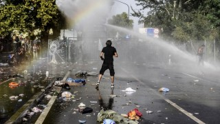 A man stands opposite Hungarian riot police using water cannon to push back refugees at the Hungarian border with Serbia near the town of Horgos on September 16, 2015. Europe's 20-year passport-free Schengen zone appeared to be a risk of crumbling with Germany boosting border controls on parts of its frontier with France as migrants desperate to find a way around Hungary's border fence began crossing into Croatia. With a string of EU countries tightened frontier controls in the face of the unprecedented human influx, the cherished principle of free movement across borders -- a pillar of the European project -- seemed in grave jeopardy. AFP PHOTO / ARMEND NIMANI
