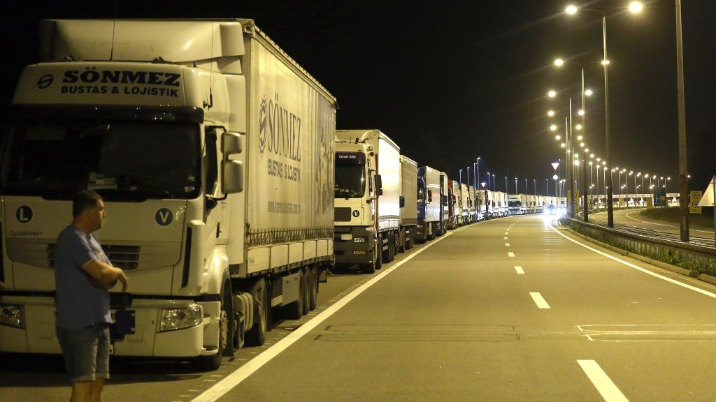 A truck driver stands in front of his vehicle at the highway on September 23, 2015, near the Batrovci border crossing between Serbia and Croatia. On Wednesday evening, Serbia banned the entry into its territory of trucks registered in Croatia and Croatian products as a counter measure against Croatia's decision to block truck traffic with Serbia. On Monday, Croatia blocked trucks coming from Serbia in a bid to pressure Belgrade to redirect the influx of migrants and refugees towards Hungary and Romania.  AFP PHOTO / OLIVER BUNIC