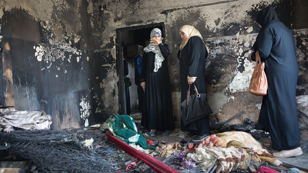 TO GO WTIH AFP STORY BY MICHEL SMITH AND SARAH BENHAIDA Palestinian women look at the damage at the Dawabsha family's home in the West Bank village of Duma on August 4, 2015, after it was set on fire by suspected Jewish extremists on July 31, 2015, killing 18-month-old Ali Saad Dawabsha and critically injuring his parents and four-year-old brother. The firebombing of the family's home in the occupied West Bank that killed the Palestinian infant sparked an international outcry over Israel's failure to curb violence by hardline Jewish settlers.  AFP PHOTO / MENAHEM KAHANA