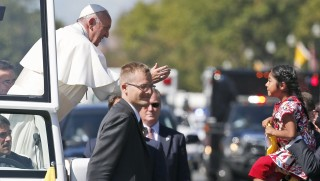 """Pope Francis reaches for five-year-old Sofia Cruz during a parade on September 23, 2015, in Washington, DC. Sofia Cruz, US-born but whose parents are from Mexico, who clambered over a barrier, darted out onto Constitution Avenue and caught the attention of Francis. She handed the pope a letter asking him to support the drive to legalize undocumented migrants living in the United States,"""" her family's parish in Los Angeles said, contacted by AFP.   AFP PHOTO / POOL / ALEX BRANDON"""