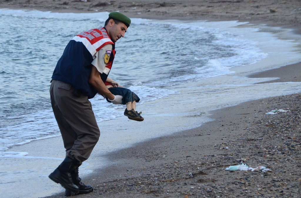 GRAPHIC CONTENT A Turkish police officer carries a migrant child's dead body off the shores in Bodrum, southern Turkey, on September 2, 2015 after a boat carrying refugees sank while reaching the Greek island of Kos. Thousands of refugees and migrants arrived in Athens on September 2, as Greek ministers held talks on the crisis, with Europe struggling to cope with the huge influx fleeing war and repression in the Middle East and Africa. AFP PHOTO / DOGAN NEWS AGENCY = TURKEY OUT =