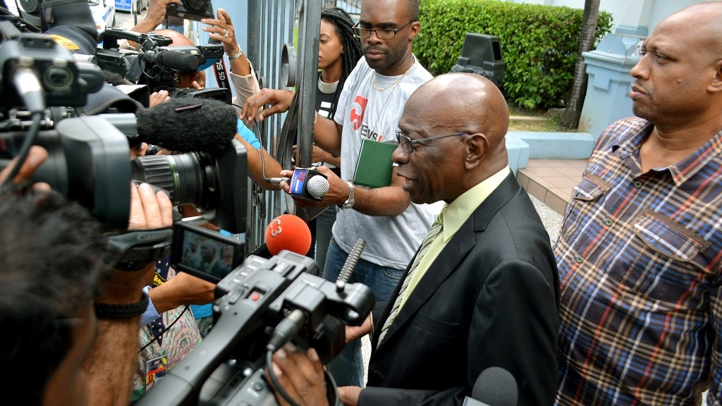 Former FIFA vice president Jack Warner(2R) talks with reporters outside the magistrates court in the capital Port-of-Spain, Trinidad, following his appearance on extradition proceedings on August 28, 2015. AFP/Alva VIARRUEL