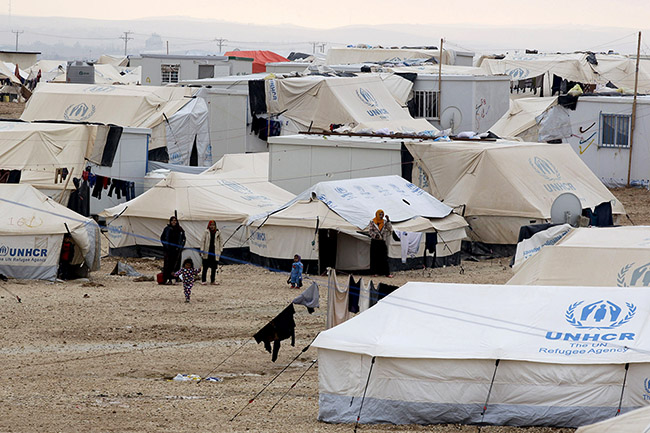 TO GO WITH AFP STORY BY MUSSA HATTAR(FILES) - A file picture taken on January 11, 2015, shows Syrian refugees standing next to tents at the UN-run Zaatari refugee camp, north east of the Jordanian capital Amman. More than 1.1 million Syrians have flooded across the border into Lebanon and around 600,000 into Jordan, according to the UNHCR on August 28, 2015. Amman puts the figure at 1.4 million, making up 20 percent of the resources-poor kingdom's population. AFP PHOTO / KHALIL MAZRAAWI