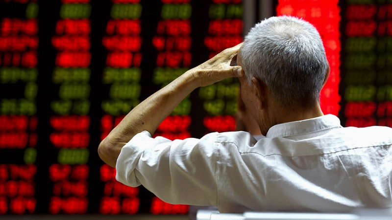An investor looks at screens showing stock market movements at a securities company in Beijing on July 14, 2015. Hundreds of firms were expected to resume trading again on July 14, adding to the more than 400 that returned July 13, after they were suspended over the past few weeks to prevent a market meltdown. Authorities intervened after the Shanghai index plunged 30 percent in three weeks, wiping trillions of dollars from market capitalisations, spreading contagion in regional markets and raising fears over the potential impact to the real economy. AFP PHOTO / GREG BAKER