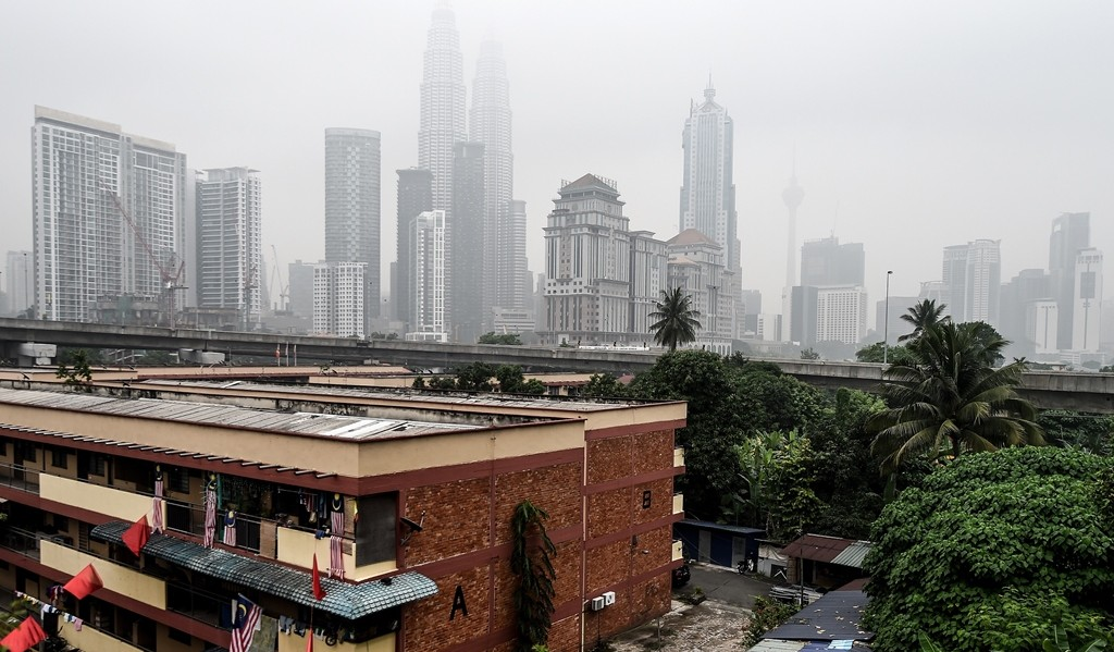 Malaysia's iconic Petronas twin towers and Kuala Lumpur's skyline are shrouded in thick haze on September 15, 2015. Malaysian authorities ordered school closures in Kuala Lumpur and neighbouring states as worsening haze from Indonesian forest and agricultural fires enveloped the capital in a smoky grey shroud.    AFP PHOTO / MANAN VATSYAYANA