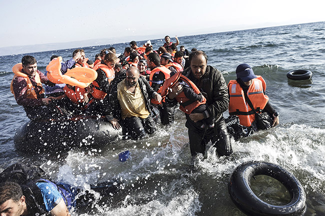 Syrian refugees arrive on the shores of Lesvos island in Greece in an inflatable boat from Turkey on August 23, 2015. AFP PHOTO / ACHILLEAS ZAVALLIS