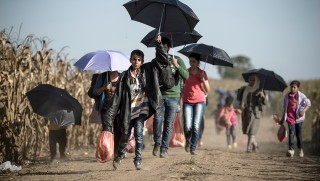 TOPSHOTSA group of migrants walk down a dirt road towards the border between Croatia and Serbia, near the western-Serbia town of Sid, on September 18 2015. Migrants have begun carving a new route into the Schengen area, traveling via Croatia, after neighboring Hungary, overwhelmed by the refugee traffic, fenced off its own border with Serbia.  AFP PHOTO / ANDREJ ISAKOVIC