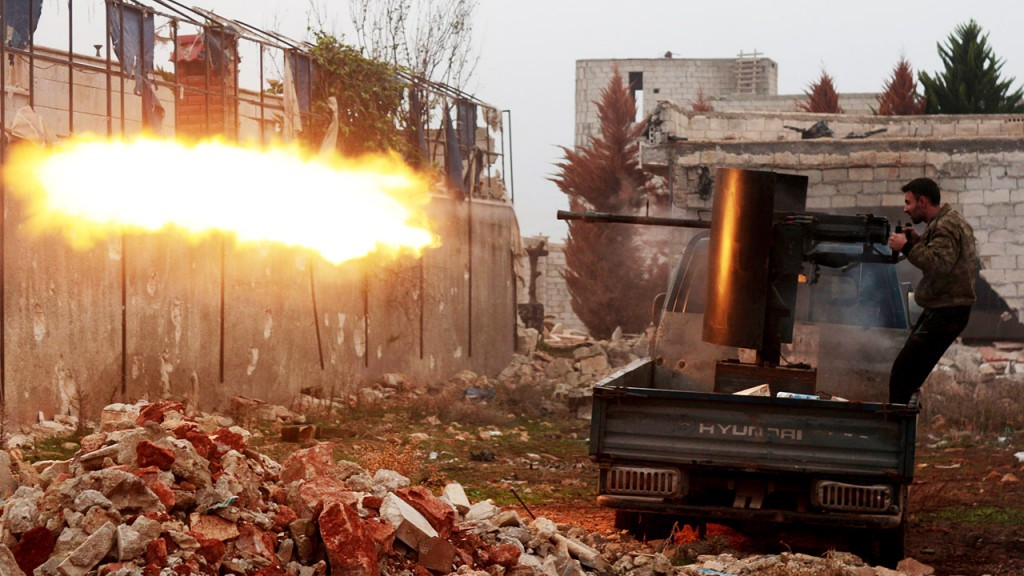 ALEPPO, SYRIA - DECEMBER 14: An Islamic Front member opens fire during the attack against Assad regime forces in the northern of Aleppo, Syria on December 14, 2014. (Photo by Ahmed Muhammed Ali/Anadolu Agency/Getty Images)