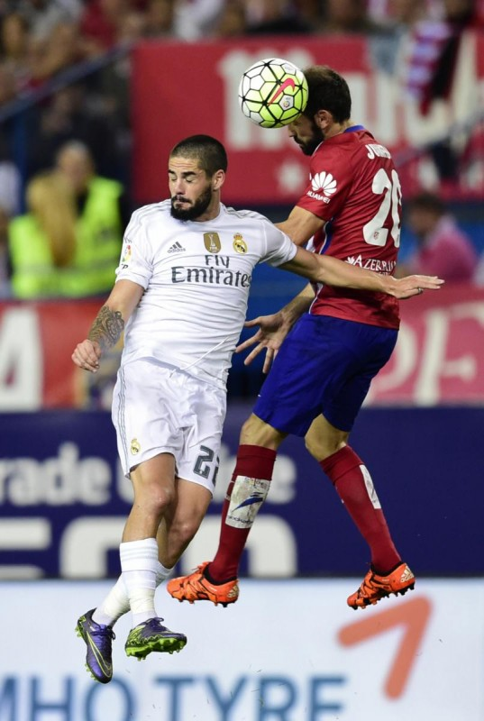 Real Madrid's midfielder Isco (L) vies with Atletico Madrid's Uruguayan defender Jose Maria Gimenez during the Spanish league football match Club Atletico de Madrid vs Real Madrid CF at the Vicente Calderon stadium in Madrid on October 4, 2015.   AFP PHOTO/ JAVIER SORIANO