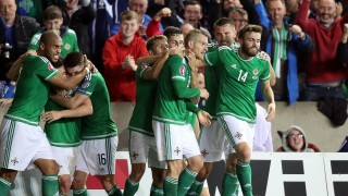 Northern Ireland's midfielder Steven Davis (C) celebrates with teammates after scoring the opening goal during the UEFA Euro 2016 qualifying Group F football match between Northern Ireland and Greece at Windsor Park in Belfast, Northern Ireland, on October 8, 2015. AFP PHOTO / PAUL FAITH