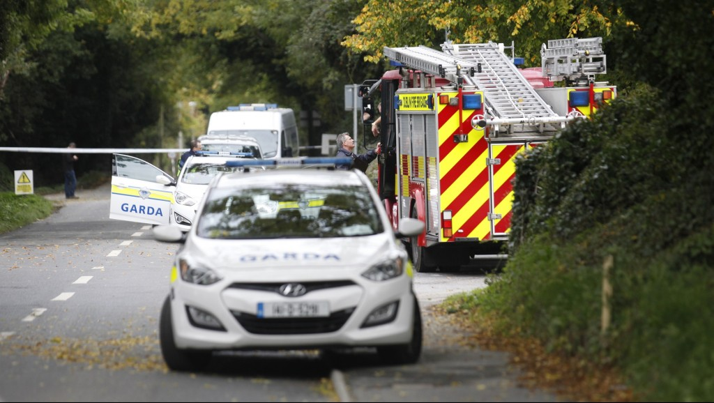 An Irish police officer talks with a fireman at the police cordon outside the halting site in the south Dublin suburb of Carrickmines, Ireland, on October 10, 2015 where a fire killed at least nine people. Nine people, including a baby and older children, have died in a fire at a site in Dublin housing members of the traveller community, police said October 10. A number of other people were taken to hospital after inhaling smoke at the site housing caravans and prefabricated buildings. AFP PHOTO