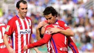 Atletico Madrid's French forward Antoine Griezmann (C) is congratulated by teammates Portuguese midfielder Tiago (R) and Uruguayan defender Diego Godin (L) after scoring during the Spanish league football match Real Sociedad de Futbol vs Club Atletico de Madrid at the Anoeta stadium in San Sebastian on October 18, 2015.   AFP PHOTO/ ANDER GILLENEA