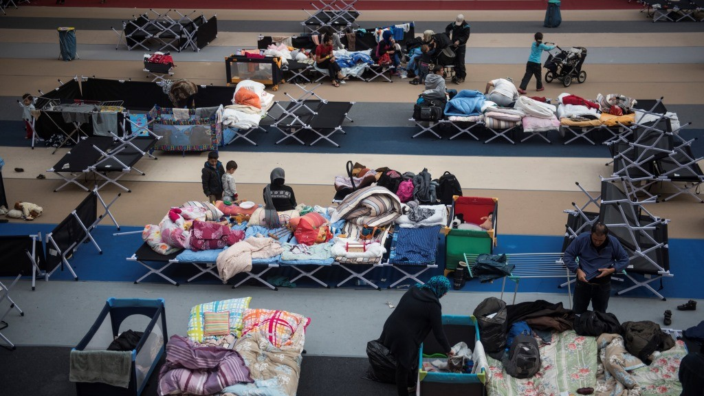 Immigrants rest on camp beds installed at the Horst Korber sports hall at the Berlin Olympic stadium complex Olympiapark on October 23, 2015. The sports centre run by private social business company Albatros GmbH houses newly arrived refugees waiting to register, providing them shelter and medical assistance.    AFP PHOTO / ODD ANDERSEN
