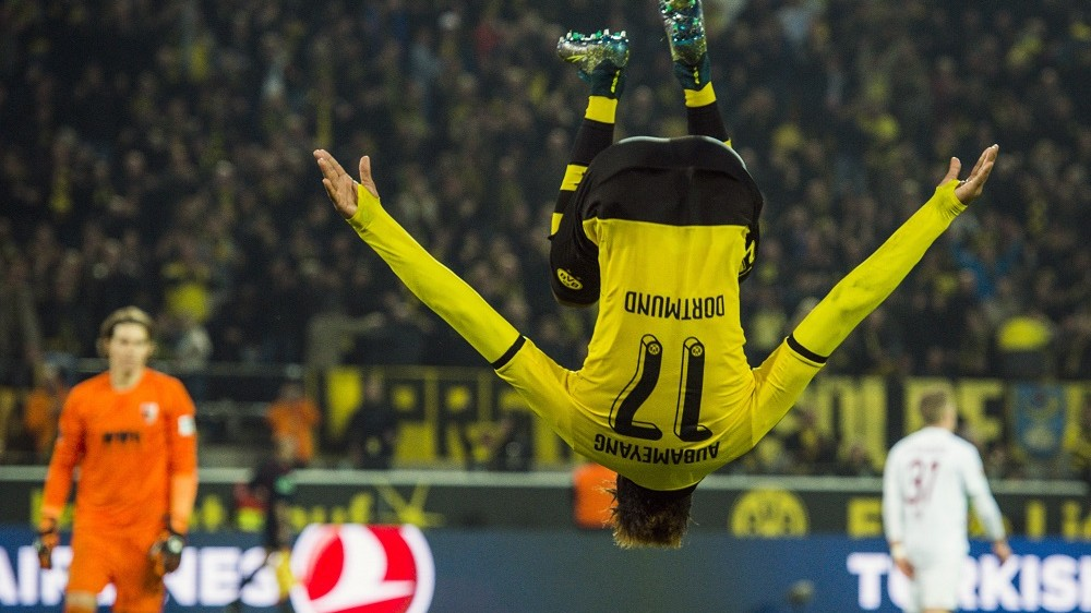 Dortmund's Gabonese midfielder Pierre-Emerick Aubameyang somersaults as he celebrates scoring his side's 5th goal to complete his hat-trick during the German first division football Bundesliga match between Borussia Dortmund and FC Augsburg on October 25, 2015 in Dortmund, western Germany. Dortmund won the match 5-1. AFP PHOTO / ODD ANDERSEN RESTRICTIONS: DURING MATCH TIME: DFL RULES TO LIMIT THE ONLINE USAGE TO 15 PICTURES PER MATCH AND FORBID IMAGE SEQUENCES TO SIMULATE VIDEO.  ==RESTRICTED TO EDITORIAL USE == FOR FURTHER QUERIES PLEASE CONTACT THE DFL DIRECTLY AT + 49 69 650050.