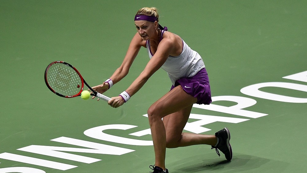 Petra Kvitova of the Czech Republic hits a return against Garbine Muguruza of Spain during their women's singles round robin tennis match at the WTA Finals in Singapore on October 30, 2015. AFP PHOTO / MOHD FYROL