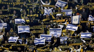 Beitar Jerusalem fans are pictured at the Teddy Stadium during their team's State Cup football match against Maccabi Umm el-Fahm, an Arab-Israeli team, on January 29, 2013, in Jerusalem. Jerusalem police deployed hundreds of forces to secure a flashpoint football match between Maccabi Umm el-Fahm and Beitar Jerusalem, a club known for its hard core of anti-Arab fans.  AFP PHOTO/STR