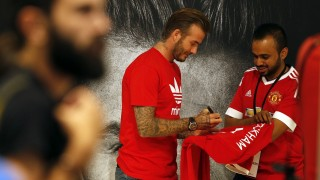 Footballing legend David Beckham signs a jersey for a fan following his arrival in Dubai's Mall of the Emirates on September 29, 2015, during a trip to the Gulf emirate. AFP PHOTO/KARIM SAHIB