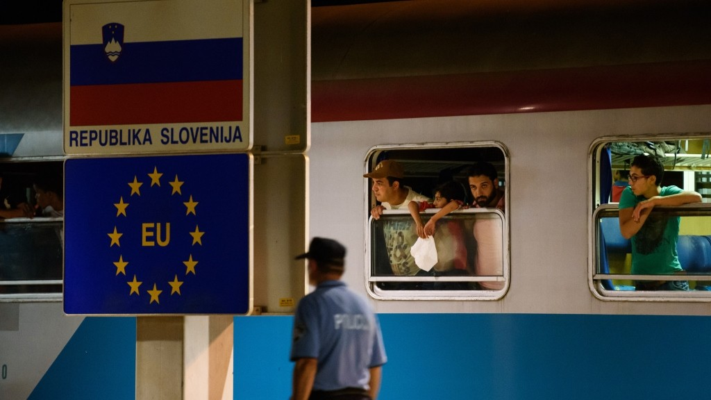 A police officer walks past migrants waiting in a train at the railway station, near the Slovenian-Croatian border in Dobova, Brezice, on September 17, 2015. Slovenia intends to reinforce its border with Croatia ahead of a possible influx of migrants seeking a new route into Europe's borderless Schengen area, the country's police chief said on September 16. Migrants have begun carving a new route into the Schengen area, travelling via Croatia, after neighbouring Hungary, overwhelmed by the refugee traffic, fenced off its own border with Serbia.  AFP PHOTO / JURE MAKOVEC