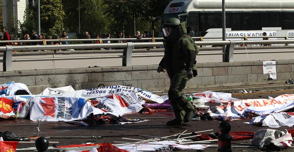 A bomb-disposal expert walks near victims' bodies covered with banners and flags, at the site of twin explosions near the main train station in Turkey's capital Ankara, on October 10, 2015. At least 86 people were killed on October 10 in the Turkish capital Ankara when bombs set off by two suspected suicide attackers ripped through leftist and pro-Kurdish activists gathering for an anti-government peace rally, the deadliest attack in the history of modern Turkey. AFP PHOTO / ADEM ALTAN