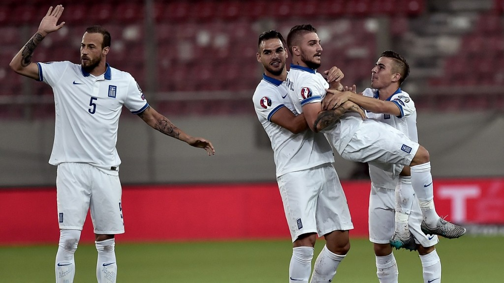 Greece's Kostas Stafylidis (2nd R) is lifted by teammate after he scored during the UEFA Euro 2016 qualifying Group F football match between Greece and Hungary at the Stadio Georgios Karaiskakis in Athens on October 11, 2015. AFP PHOTO / ANGELOS TZORTZINIS