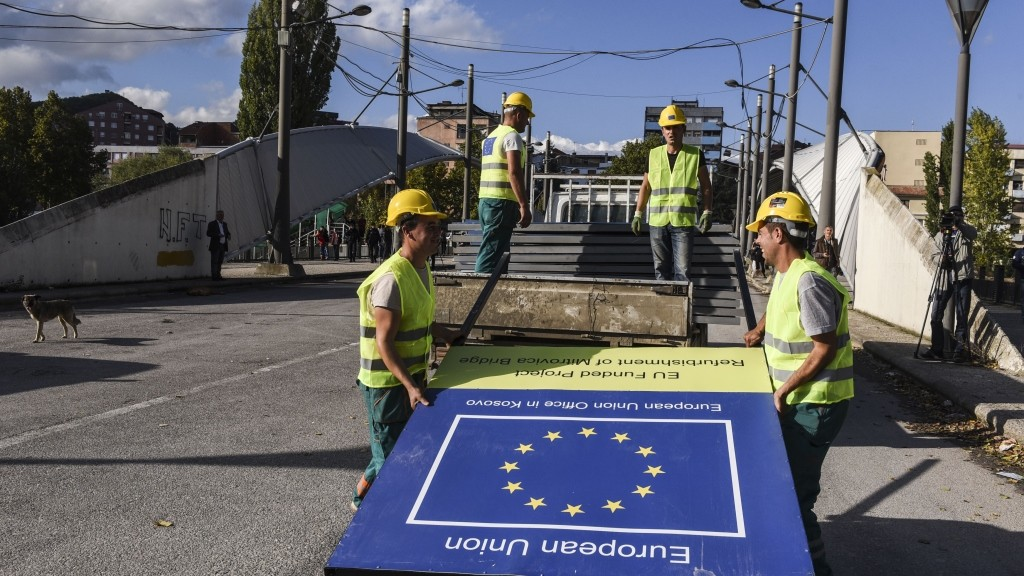 Construction employees unload metal panels during the reconstruction of the main bridge of the divided town of Mitrovica on October 17, 2015. Kosovo's Prime Minister Isa Mustafa mentioned that the bridge will be open for traffic on June 2016. AFP PHOTO/ARMEND NIMANI