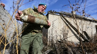 TO GO WITH AFP STORY BY NICOLAS MILETITCH Pro-Russian rebel sapper Konstantin, 42 years old, carries an unexploded shell in Veseloe village, near Donetsk on October 18, 2015. While gunfires almost stopped after the ceasefire reached in September, the shells, mines and booby traps continue to cause every week the death of several civilians and soldiers on both sides. AFP PHOTO/ALEXEY FILIPPOV