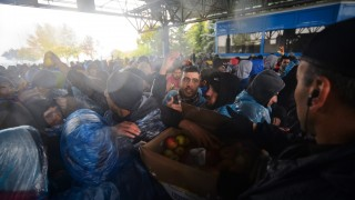 Migrants receive apple as they wait to enter Slovenia, at the Croatian-Slovenian border in Trnovec, on October 19, 2015. Slovenian authorities said today they had refused to let in more than 1,000 migrants arriving from Croatia after a daily quota had been reached, stoking fears of a new human bottleneck on the western Balkan route.  AFP PHOTO / JURE MAKOVEC