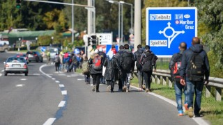 Migrants and asylum seekers walk to cross the Slovenian-Austrian border in Sentilj to continue their journey onto Spielfeld on October 21, 2015. Tens of thousands -- many fleeing violence in Syria, Africa and Afghanistan -- have been making their way from Turkey to the Balkans in recent months, hoping to reach Germany, Sweden and other EU states. AFP PHOTO / JURE MAKOVEC