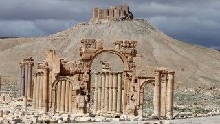 (FILES) - A file picture taken on March 14, 2014 shows the famous Arch of Triumph (front) and a partial view of the ancient oasis city of Palmyra, 215 kilometres northeast of the Syrian capital, Damascus. Islamic State extremists have blown up the famous Arch of Triumph in the ancient Syrian city of Palmyra, said an activist and monitoring group, as the jihadists press their campaign to tear down the treasured heritage site. AFP PHOTO/JOSEPH EID