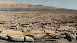 """This NASA image obtained October 9, 2015 shows a view from the """"Kimberley"""" formation on Mars taken by NASA's Curiosity rover. The strata in the foreground dip towards the base of Mount Sharp, indicating flow of water toward a basin  that existed before the larger bulk of the mountain formed.The colors are adjusted so that rocks look approximately as they would if they were on Earth, to help geologists interpret the rocks. This """"white balancing"""" to adjust for the lighting on Mars overly compensates for the absence of blue on Mars, making the sky appear light blue and sometimes giving dark, black rocks a blue cast.This image was taken by the Mast Camera (Mastcam) on Curiosity on the 580th Martian day, or sol, of the mission. NASA on October 9, 2015 outlined the many challenges that remain before humans can set foot on Mars, calling the problems """"solvable"""" but setting no firm date for an astronaut mission to the Red Planet. AFP PHOTO/NASA/JPL-CALTECH/MSSS"""