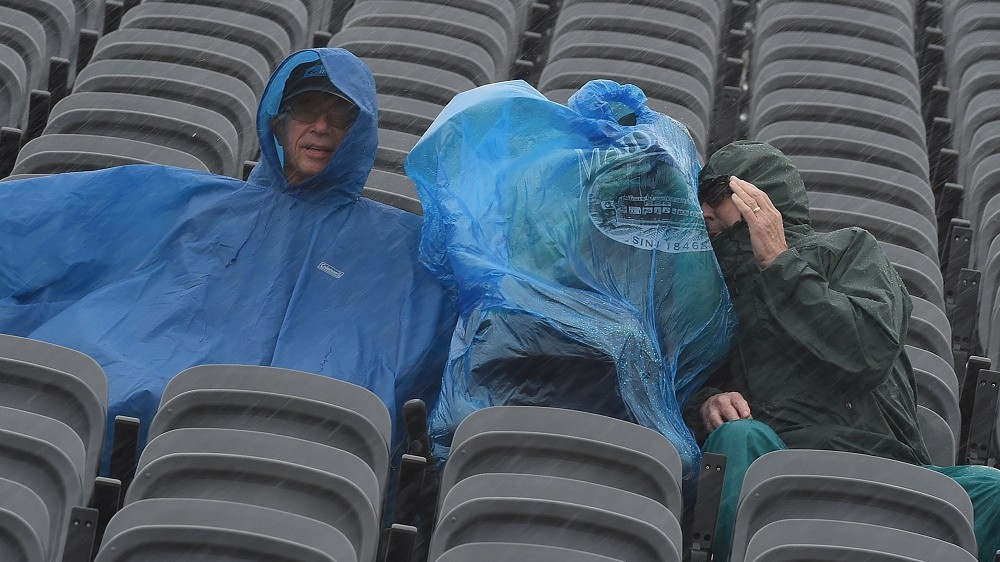 Fans shelter from heavy rain as they wait for the qualifying session of the United States Formula One Grand Prix at the Circuit of The Americas in Austin, Texas on October 24, 2015.                        AFP PHOTO / MARK RALSTON