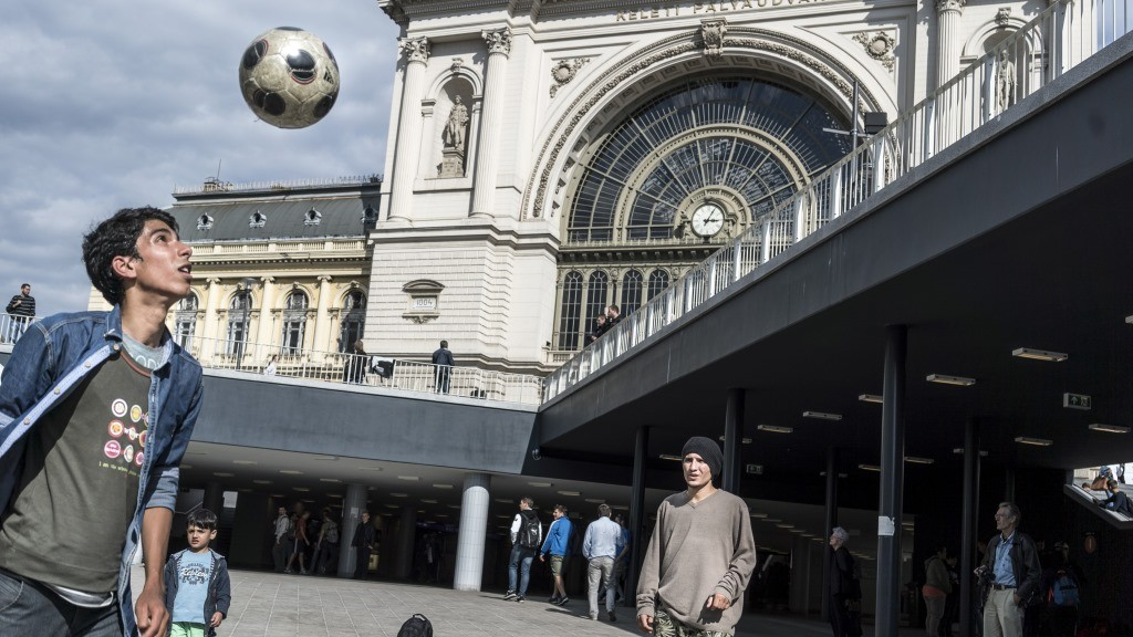 HUNGARY, Roszke: Young boys play football as refugees crowd Budapest's Keleti Train Station on September 8 2015, as Europe's refugee crisis continues.  - CITIZENSIDE/FÁBIO ERDOS