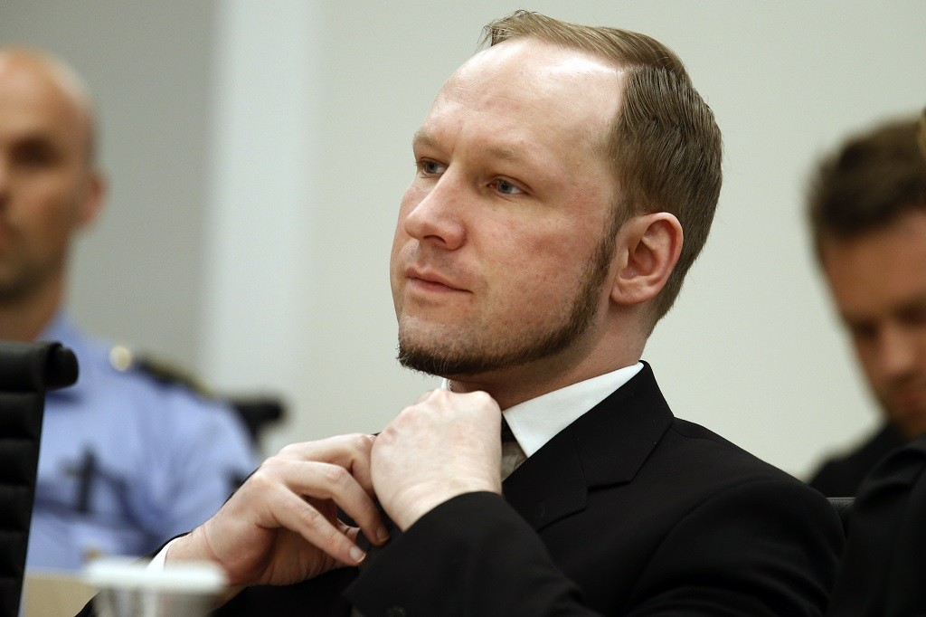 """(FILES) This picture taken on August 24, 2012 shows self confessed mass murderer Anders Behring Breivik adjusting his tie in court room 250 at Oslo District Court, Norway. Mass murderer Anders Behring Breivik will take the Norwegian state to court in March 2016 over his prison conditions, which he likens to """"torture"""", Norwegian legal sources said on October 16, 2015.  AFP PHOTO / POOL / HEIKO JUNGE"""