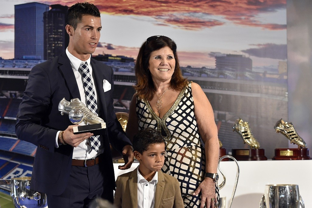 Real Madrid's forward Portuguese Cristiano Ronaldo (L) poses with his son Cristiano Jr and his mother Maria Dolores dos Santos Aveiro (R) during a ceremony for becoming Real Madrid's all-time leading scorer at the Santiago Bernabeu stadium in Madrid on October 2, 2015. Cristiano Ronaldo surpassed 500 career goals and tied Raul as Real Madrid's all-time leading scorer with a double in the Spanish giants 2-0 win away at Malmo on September 30, 2015. AFP PHOTO / GERARD JULIEN