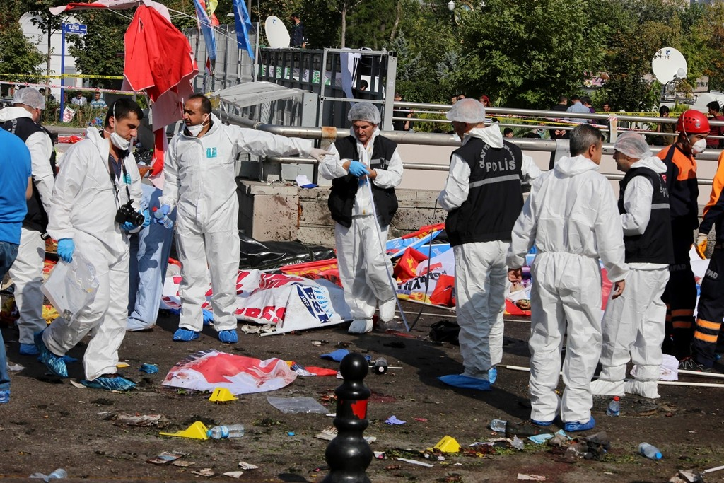Members of a Police forensic teema gather evidence at the site of twin explosions at the main train station in Turkey's capital Ankara, on October 10, 2015. At least 30  people were killed and 126 were injured in the blasts which happened ahead of an anti-government peace rally organised by leftist groups later in the day, including the pro-Kurdish Peoples' Democratic Party (HDP).  AFP PHOTO / ADEM ALTAN