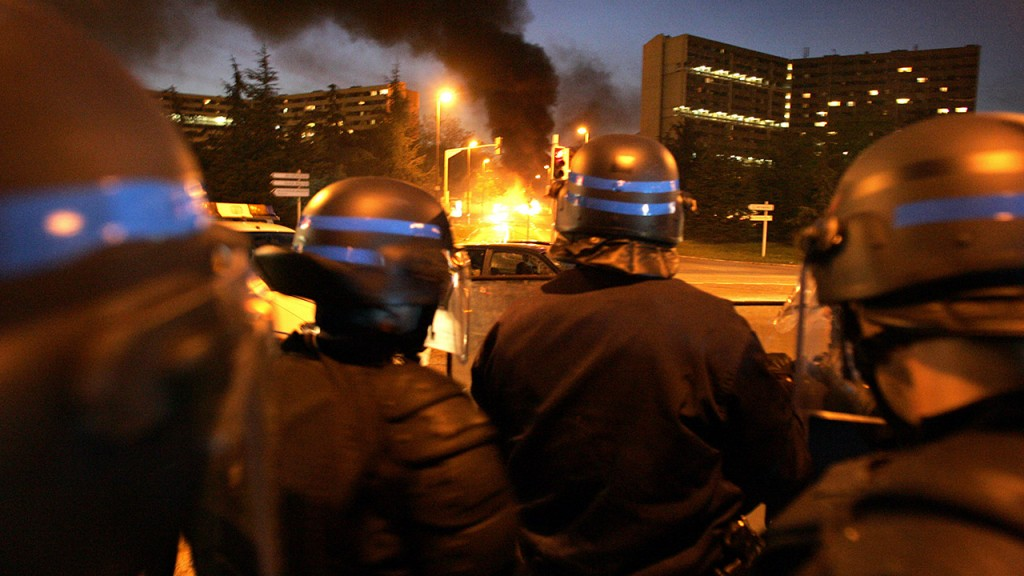 """Policemen stand guard as a bus is burning at the entrance of """"Le Mirail"""", a sensitive neighbourghood of Toulouse, west southern France, 07 November 2005. The riots spreading across France claimed their first fatality today, with the death of a 61-year-old man who was in a coma after being assaulted on a housing estate north of Paris last week. Two police officers were hospitalised after being hit by gun-shots in what colleagues said was an ambush by a gang of youths in Grigny. The unrest was sparked October 27 by the electrocution deaths of two teenagers who hid in an electrical sub-station in northeastern Paris to escape a police identity checkAFP PHOTO LIONEL BONAVENTURE"""