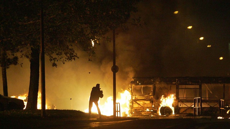 """A person throws a molotov cocktail to policemen as a bus is burning at the entrance of """"Le Mirail"""", a sensitive neighbourghood of Toulouse, west southern France, 07 November 2005. The riots spreading across France claimed their first fatality today, with the death of a 61-year-old man who was in a coma after being assaulted on a housing estate north of Paris last week. Two police officers were hospitalised after being hit by gun-shots in what colleagues said was an ambush by a gang of youths in Grigny. The unrest was sparked October 27 by the electrocution deaths of two teenagers who hid in an electrical sub-station in northeastern Paris to escape a police identity checkAFP PHOTO LIONEL BONAVENTURE"""