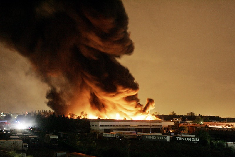 Picture shows a warehouse bruning in the early hours of 04 November 2005 in Aulnay-sous-Bois on the seventh consecutive night of violence on the ouskirts of the French capital. More than 1,300 police were deployed to again do battle with groups of stone- and bottle-throwing youths that have torched hundreds of vehicles and vandalised buildings in rampages in low-income, high-immigrant districts since 27 October following a reportedly accidental electrocution of two teenagers who had hidden in an electrical sub-station to escape a police identity check in the suburb at the epicentre of the troubles, Clichy-sous-Bois.  AFP PHOTO JACK GUEZ