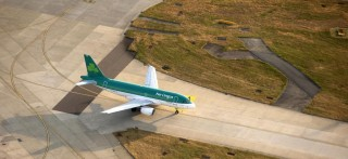 An Aer Lingus aircraft, operated by Aer Lingus Group Plc, stands on the perimeter of the runway at London Heathrow Airport, in this aerial photograph taken over London, U.K., on Tuesday, June 16, 2015. Europe's largest hub at London Heathrow, which has been operating close to capacity since the start of the decade, and rival Gatwick have been short-listed for a new runway by the state-appointed Davies Commission, with a final recommendation due in coming weeks. Photographer: Matthew Lloyd/Bloomberg