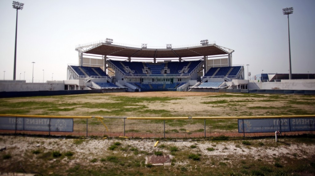 An overgrown softball pitch and empty spectator stand is seen at the 2004 Olympic complex at Hellinikon, near Athens, Greece, on Wednesday, March 21, 2012. Greek Prime Minister Lucas Papademos won parliamentary approval for a new 130 billion-euro ($172 billion) international bailout that will keep the country's possible financial collapse at bay. Photographer: Kostas Tsironis/Bloomberg via Getty Images